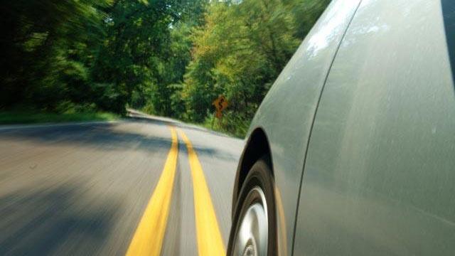 green hybrid car driving down road_487591001125436-159532