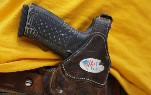 FILE - In this April 14, 2018 file photo, a man wears an unloaded pistol during a pro gun-rights rally in Austin, Texas. (AP Photo/Eric Gay, File)