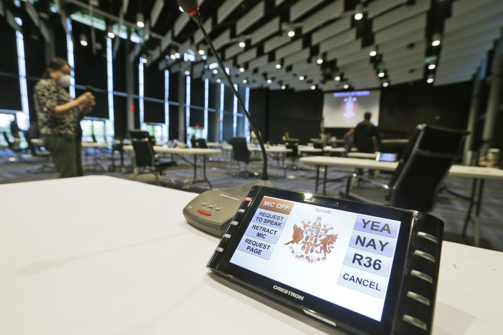 A Senate voting device is set up by Virginia Senate staff at the temporary site where the Virginia Senate will meet for the reconvene session at the Science Museum Monday April 20, 2020, in Richmond, Va. (AP Photo/Steve Helber)