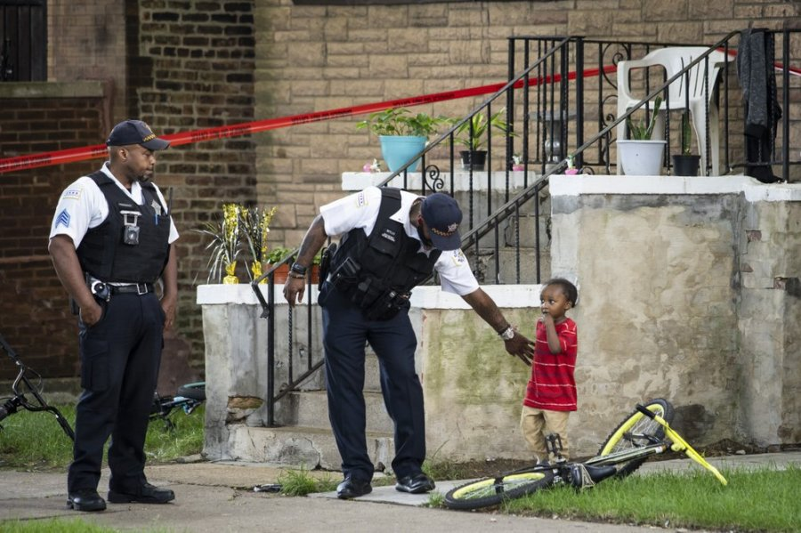 A Chicago police officer helps a child walk through an area being investigated after two men were shot Friday, July 3, 2020, in Chicago. At least 13 people were killed in Chicago over the Fourth of July weekend, police said. At least 59 others were shot and wounded. (Ashlee Rezin Garcia/Chicago Sun-Times via AP)